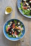 Roast beetroot, figs and feta salad. Autumn salad with roast beetroot, figs and feta cheese on the bed of green mixed salad leaves stock images