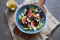 Roast beetroot, figs and feta salad. Autumn salad with roast beetroot, figs and feta cheese on the bed of green mixed salad leaves stock photo
