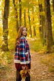 Autumn sale. Beautiful happy smiling girl with long hair wearing stylish jacket posing in autumn day. Autumn portrait. Smiling woman holds yellow maple leaves stock image