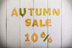 Autumn sale 10 percent. The text `autumn sale 10 percent,` cut from different yellow and orange fallen leaves from the trees and laid on the white wooden boards Royalty Free Stock Photography
