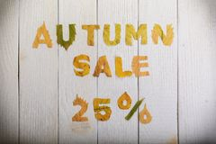 Autumn sale 25 percent. The text `autumn sale 25 percent,` cut from different yellow and orange fallen leaves from the trees and laid on the white wooden boards Royalty Free Stock Images