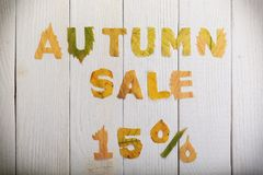Autumn sale 15 percent. The text `autumn sale 15 percent,` cut from different yellow and orange fallen leaves from the trees and laid on the white wooden boards Stock Photo