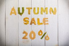 Autumn sale 20 percent. The text `autumn sale 20 percent,` cut from different yellow and orange fallen leaves from the trees and laid on the white wooden boards Stock Photography