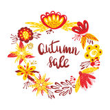 Autumn Sale. The trend calligraphy text in wreath from autumn leaves and flowers. Beautiful round wreath of autumn leaves. Stock Photo