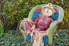 Autumn scarecrow in wicker chair Stock Images