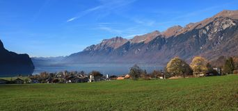 Autumn scene in Brienz. Green meadow, houses and lake Brienzerse. Lake Brienzersee and mount Augstmatthorn. View from Brienz, Switzerland Stock Photos