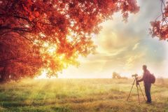 Autumn scene with photographer. Colorful autumn background with traveler. Magic place in nature in autumn Stock Images