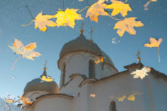 Autumn scene - reflection in a puddle of St Sophia cathedral with fallen autumn leaves in Veliky Novgorod, Russia. Autumn landscape of Veliky Novgorod Stock Photography