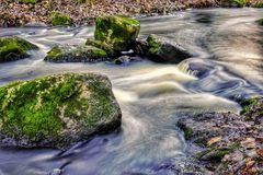 Autumn scene in small river. Moss covered rocks in streaming water. Sun reflecting from water stock images