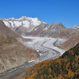 Autumn scene in Valais, Switzerland. Colorful forest, Aletsch glacier and mountains. stock photo