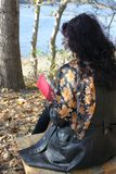 Autumn scene with a woman. Autumn scene in the forest with a woman in front of a lake holding a red book stock photos