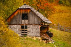 Autumn scenery landscape with colorful forest, wood fences and abandoned hay barn in Prisaca Dornei. Suceava County, Bucovina, Romania Stock Photography