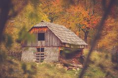 Autumn scenery landscape with colorful forest, wood fences and abandoned hay barn in Prisaca Dornei. Suceava County, Bucovina, Romania Stock Photo