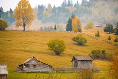 Autumn scenery landscape with colorful forest, wood fences and hay barns in Bucovina, Romania. Autumn scenery landscape with colorful forest, wood fences and hay Royalty Free Stock Photos