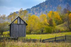 Autumn scenery landscape with colorful forest, wood fences and hay barns in Bucovina, Romania. Autumn scenery landscape with colorful forest, wood fences and hay Stock Photo