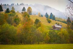 Autumn scenery landscape with colorful forest, wood fences and hay barns in Bucovina, Romania. Autumn scenery landscape with colorful forest, wood fences and hay Royalty Free Stock Images