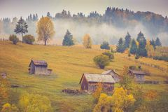 Autumn scenery landscape with colorful forest, wood fences and hay barns in Bucovina, Romania. Autumn scenery landscape with colorful forest, wood fences and hay Stock Image