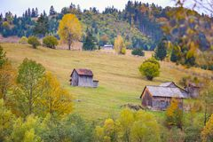 Autumn scenery landscape with colorful forest, wood fences and hay barns in Bucovina, Romania. Autumn scenery landscape, colorful forest, wood fences and hay Stock Images
