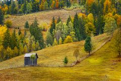 Autumn scenery landscape with colorful forest, wood fences and hay barns in Prisaca Dornei. Suceava County, Bucovina, Romania Stock Photos