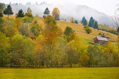 Autumn scenery landscape with colorful forest, wood fences and hay barns in Bucovina, Romania Stock Photography
