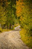 Autumn scenery landscape with rural road, colorful forest, wood fences and hay barns in Bucovina Stock Image