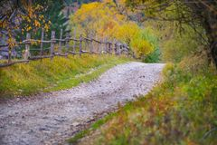 Autumn scenery landscape with rural road, colorful forest, wood fences and hay barns in Bucovina Royalty Free Stock Photo