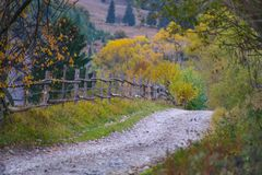 Autumn scenery landscape with rural road, colorful forest, wood fences and hay barns in Bucovina. Autumn scenery landscape with rural road, colorful forest, wood Stock Photo
