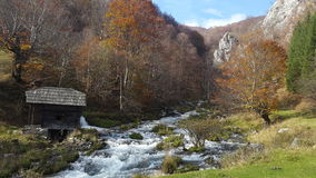 Autumn scenery with small cottage. A beautiful scene at the springs of Cerna River in Romania with a small cottage on the bank Stock Photos
