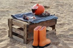 Autumn scenery on the wine box on the beach. Autumn scenery with pumkin and rain boots in the box after the wine on the beach Royalty Free Stock Photography