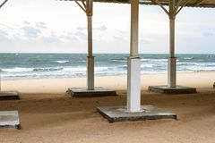 Autumn sea cold stormy blue and green waves, white foam and clouds on sandy beach view through the empty bathing roof . Black Sea. Autumn sea cold stormy blue stock photography