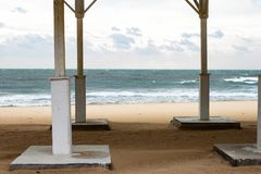 Autumn sea cold stormy blue and green waves, white foam and clouds on sandy beach view through the empty bathing roof . Black Sea. Autumn sea cold stormy blue royalty free stock photography