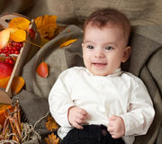 Autumn season, child boy lie on yellow fall leaves, apples, pumpkin and decoration on textile Stock Photo