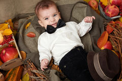 Autumn season, child boy lie on yellow fall leaves, apples, pumpkin and decoration on textile Stock Image