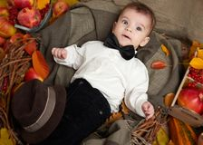 Autumn season, child boy lie on yellow fall leaves, apples, pumpkin and decoration on textile Royalty Free Stock Photography