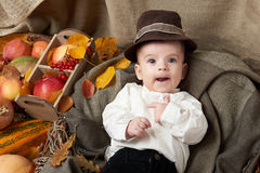 Autumn season, child boy lie on yellow fall leaves, apples, pumpkin and decoration on textile Royalty Free Stock Photo