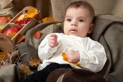 Autumn season, child boy lie on yellow fall leaves, apples, pumpkin and decoration on textile Royalty Free Stock Photos