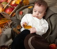 Autumn season, child boy lie on yellow fall leaves, apples, pumpkin and decoration on textile Royalty Free Stock Image