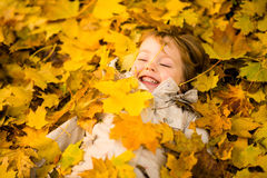 Autumn season - child in fallen leaves Stock Images