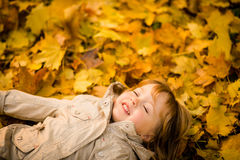 Autumn season - daydream. Little child daydreaming with closed eyes lying in fallen leaves in autumn Royalty Free Stock Photo