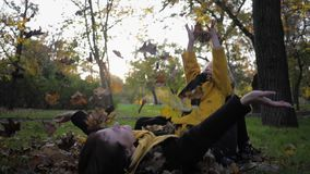 Autumn season, happy mother with a cute daughter lie on lawn in autumn park and throw leaves during a garden walk