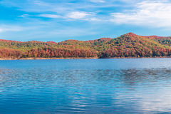 Autumn season at lake with beautiful forest at hill shore. Stock Photos