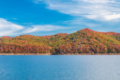 Autumn season at lake with beautiful forest at hill shore. Royalty Free Stock Image