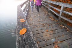 Autumn season people walking. Blurry family walking on aged wooden bridge floor with colorful autumn season leaves on the ground. People walking alone across the Stock Images