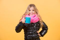 Autumn season relax concept. Child hold mug in black jacket and pink scarf. Tea or coffee break. Hot drink in cold weather. Girl with blue cup smile on orange Stock Photos
