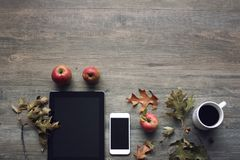 Autumn season still life with red apples, mobile devices, black coffee cup and fall leaves over rustic wooden background. Knolling Stock Photos