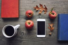 Autumn season still life with red apples, books, mobile device, black coffee cup and fall leaves over rustic wooden background. Kn Stock Image