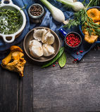 Autumn seasonal cooking ingredients with harvest vegetables, greens and mushrooms on dark rustic wooden background. Top view stock photography