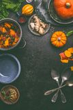 Autumn seasonal food background with pumpkin. Dark rustic kitchen table with tools, bowls, spoons Stock Images