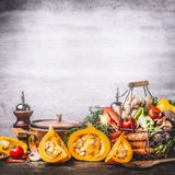 Autumn seasonal food still life with pumpkin, mushrooms, various organic harvest vegetables and cooking pot on rustic kitchen tabl. E background, front view stock photos
