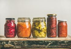 Autumn pickled colorful vegetables in jars placed in row. Autumn seasonal pickled or fermented colorful vegetables in jars placed in row over vintage kitchen Royalty Free Stock Photo
